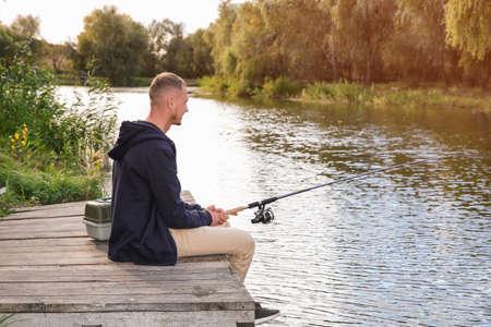 Man fishing on wooden pier at riverside. Recreational activity