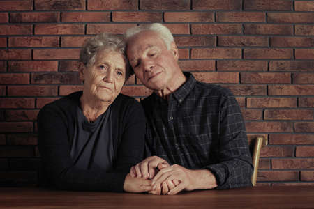 Poor elderly couple sitting and holding hands at table