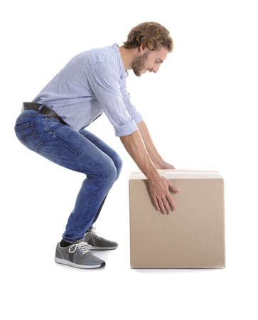 Full length portrait of young man lifting heavy cardboard box on white background. Posture concept