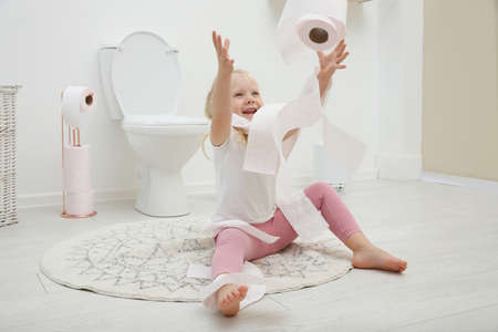 Cute little girl playing with toilet paper in bathroom Stok Fotoğraf