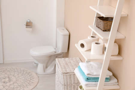 Toilet paper rolls on shelving unit in bathroom. Space for text