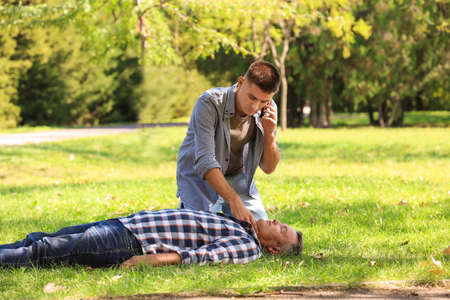 Passerby calling ambulance while checking pulse of unconscious man outdoors. First aid Stock Photo - 112087269