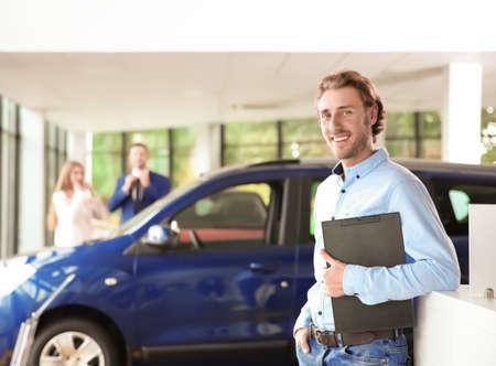 Salesman with clipboard near new car in modern auto dealership 版權商用圖片