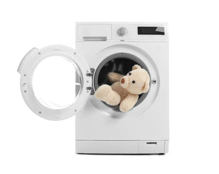 Modern washing machine with teddy bear on white background. Laundry day