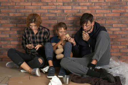 Poor homeless family sitting on floor near brick wall
