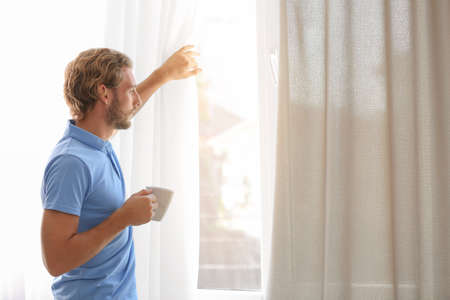 Young man having rest near window with open curtains at home