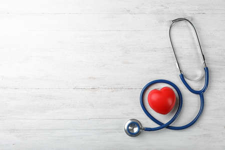 Stethoscope for checking pulse and red heart on light background, top view. Space for text