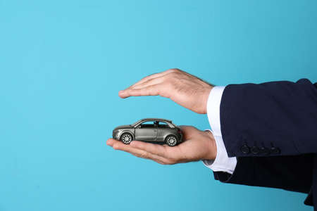 Male insurance agent holding toy car on color background, closeup. Space for text