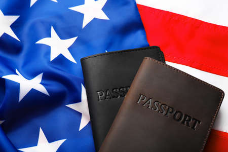 Passports in leather covers on flag of USA, top view
