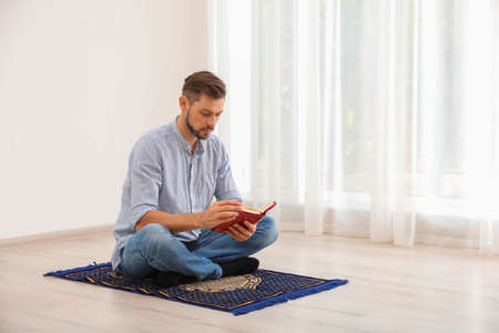 Muslim man reading Koran on prayer rug indoors Imagens