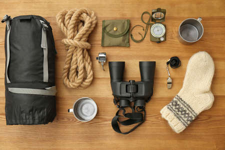 Flat lay composition with sleeping bag and camping equipment on wooden background