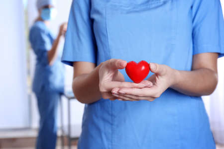 Doctor holding red heart at hospital, closeup. Donation day