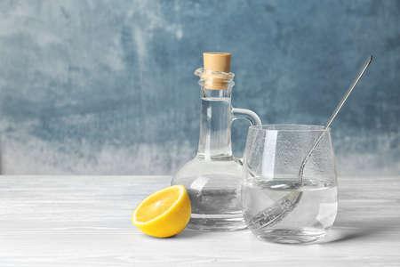 Composición con vinagre y limón sobre mesa. Espacio para texto Foto de archivo