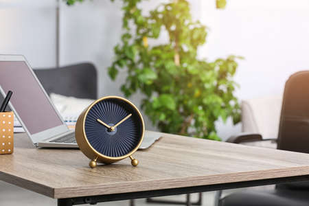 Workplace with stylish analog clock and laptop in office. Space for text Standard-Bild