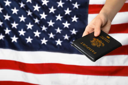 Woman holding passport against flag of USA, closeup with space for text