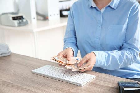 Cassiere femminile con soldi al reparto cassa, primo piano