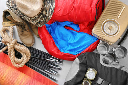 Flat lay composition with sleeping bag and camping equipment on grey background Imagens