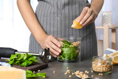 Woman making basil pesto sauce at kitchen table Stock Photo