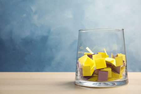 Colorful paper pieces for lottery in glass vase on table. Space for text
