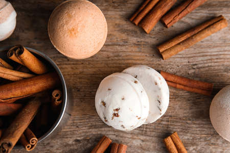 Bath bombs with cinnamon sticks on wooden table, top view