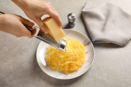 Kobieta ściera ser na gotowanej dyni spaghetti na stole, zbliżenie Zdjęcie Seryjne