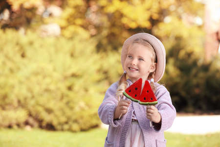 Cute little girl with tasty candies outdoors