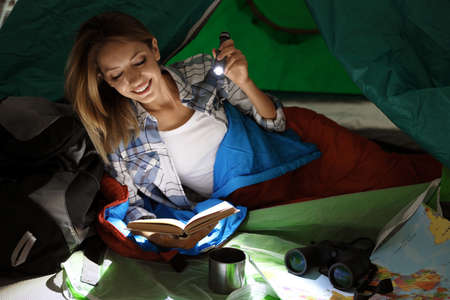 Young woman in sleeping bag reading book with flashlight inside of tent Stock Photo - 112345725