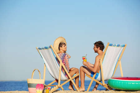 Young couple in beach chairs at seacoast