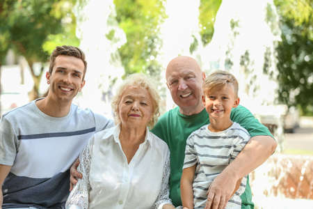 Man with son and elderly parents outdoors