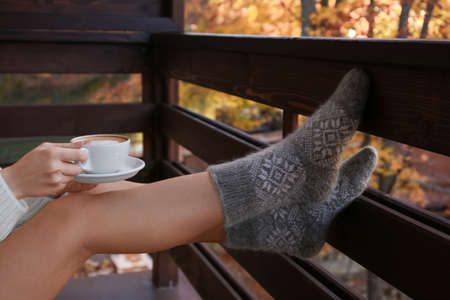 Woman in warm woolen socks with cup of hot cozy drink on balcony Imagens