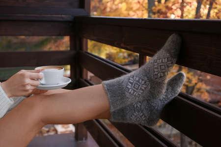 Woman in warm woolen socks with cup of hot cozy drink on balcony Reklamní fotografie