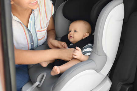 Mother fastening baby to child safety seat inside of car Imagens