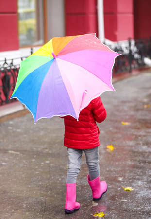 Little girl with umbrella taking autumn walk in city on rainy day Stock Photo