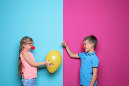 Children making balloon explosion joke on color background. April Fool's Day