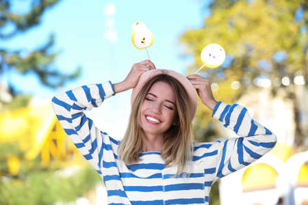 Young happy woman with sweet candies outdoors