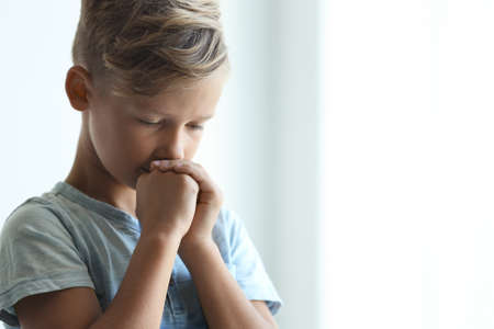 Little boy with hands clasped together for prayer on light background. Space for text Stock Photo