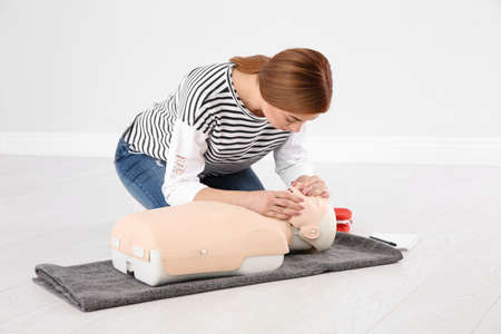 Woman practicing first aid on mannequin indoors