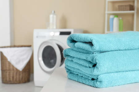 Stack of clean soft towels on table in laundry room. Space for text Stockfoto