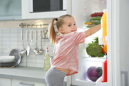 Cute girl choosing food from refrigerator in kitchen