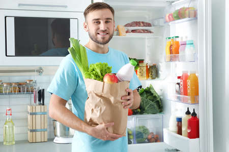 Man with bag of products standing near refrigerator in kitchen