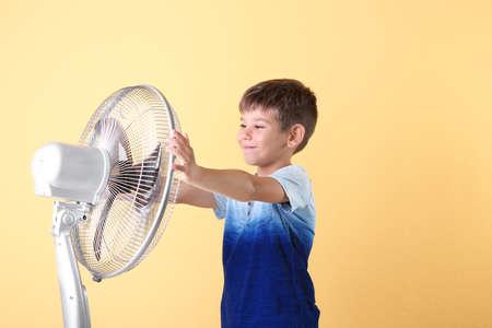 Kleiner Junge, der sich von der Hitze vor dem Ventilator auf farbigem Hintergrund erfrischt Standard-Bild