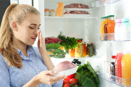 Woman taking stale meat out of refrigerator in kitchen