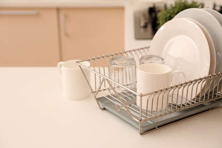 Dish drainer with clean dinnerware on table in kitchen. Space for text Standard-Bild - 112069542