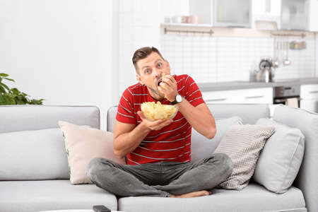 Man with bowl of potato chips sitting on sofa in living room Stock Photo