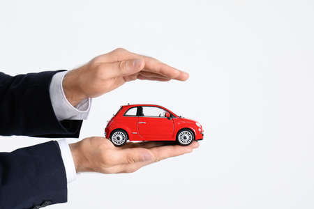 Male insurance agent holding toy car on white background, closeup. Space for text
