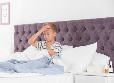 Ill boy suffering from cough in bed at home