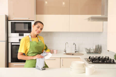 Young woman wiping clean plate in kitchen. Dish washing