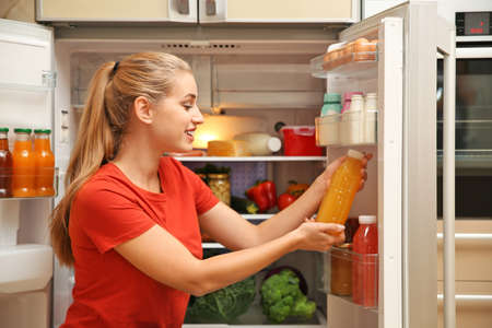 Young woman with juice near refrigerator at home