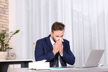 Ill businessman suffering from cough in office