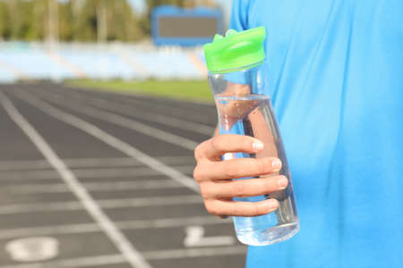 Sporty man holding bottle of water at stadium on sunny day, closeup. Space for text